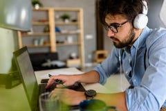 Le jeune homme d'affaires barbu s'assied devant l'ordinateur, fonctionnant L'ind?pendant, entrepreneur travaille ? la maison image stock