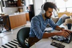 Le jeune homme d'affaires barbu s'assied devant l'ordinateur, fonctionnant L'ind?pendant, entrepreneur travaille ? la maison images libres de droits