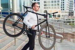 Le jeune homme d'affaires beau dans une chemise blanche et un lien noir porte son vélo photographie stock libre de droits