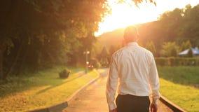 Le jeune homme d'affaires beau marche et détend au parc sur le coucher du soleil d'or Vue arrière banque de vidéos