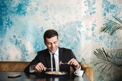 Le jeune homme d'affaires beau s'asseyant en café prennent un petit déjeuner ou le dîner mangent images stock