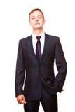 Le jeune homme d'affaires bel dans le costume noir se tient directement, portrait d'isolement sur le fond blanc Image stock