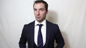 Le jeune homme d'affaires bel nettoie et ajuste son costume, souriant regardant la caméra banque de vidéos