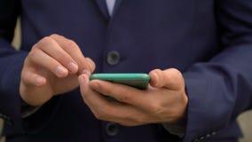 Le jeune homme d'affaires communique dans les réseaux sociaux sur son smartphone banque de vidéos