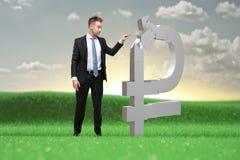 Le jeune homme d'affaires décide quoi faire avec les capitaux de rouble image stock