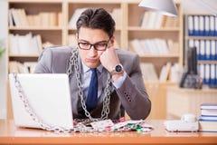 Le jeune homme d'affaires dépendant au jeu en ligne carde jouer dans t photo stock
