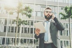 Le jeune homme d'affaires dans le costume et le lien se tient extérieur, tient la tablette et parle à son téléphone portable images libres de droits