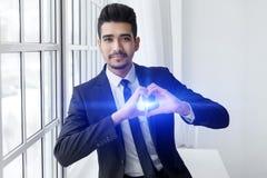 Le jeune homme d'affaires dans l'amour montre le signe de coeur Images libres de droits