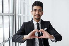 Le jeune homme d'affaires dans l'amour montre le signe de coeur Photos stock