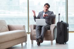 Le jeune homme d'affaires dans le vol de attente de salon d'affaires d'aéroport Photographie stock