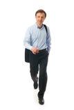 Le jeune homme d'affaires de marche d'isolement sur un blanc Images stock