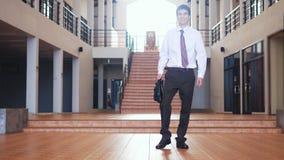 Le jeune homme d'affaires de sourire bel dans un costume marche avec une serviette à un centre d'affaires Communication, contacts photo libre de droits