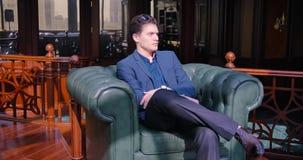 Le jeune homme d'affaires de type attendant un associé, regarde sa montre Retard sur l'affaire, appartement chic, non banque de vidéos