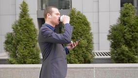 Le jeune homme d'affaires descendant la rue avec les ?couteurs sans fil dans les oreilles et ?crit un message au t?l?phone clips vidéos
