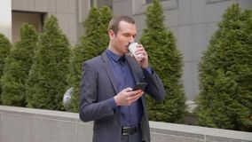 Le jeune homme d'affaires descendant la rue avec un verre de caf? dans sa main ?crit un message au t?l?phone banque de vidéos
