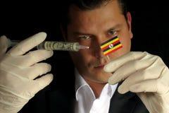 Le jeune homme d'affaires donne une injection financière au drapeau ougandais est Images libres de droits