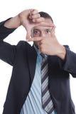 Le jeune homme d'affaires effectuent le signe d'orientation avec ses mains Photographie stock libre de droits