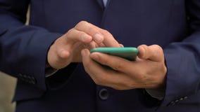Le jeune homme d'affaires emploie l'application sur son smartphone banque de vidéos