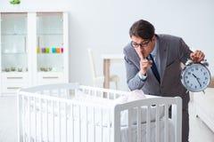 Le jeune homme d'affaires essayant de travailler de la maison s'inquiétant après bébé nouveau-né Photos stock