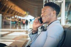Le jeune homme d'affaires est assis dans l'aéroport souriant et parlant b images libres de droits