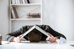 Le jeune homme d'affaires fatigué se trouve sur la table avec l'ordinateur portable photographie stock
