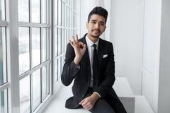 Le jeune homme d'affaires montre le signe correct, réussite commerciale Photographie stock libre de droits