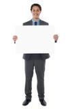 Le jeune homme d'affaires retient le panneau-réclame blanc Image stock
