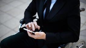Le jeune homme d'affaires s'asseyant sur le fauteuil roulant est jouant ou travaillant avec son smartphone clips vidéos