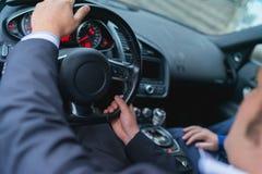 Le jeune homme d'affaires sûr exploite une voiture de sport puissante Image stock