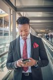 Le jeune homme d'affaires se lève en dehors de l'aéroport regardant le Th photographie stock