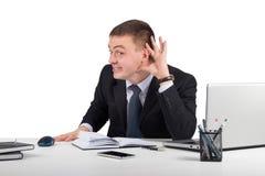 Le jeune homme d'affaires tient sa main près de l'oreille Image stock