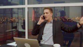 Le jeune homme d'affaires a une conversation désagréable au téléphone portable banque de vidéos