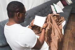 Le jeune homme d'Afro-américain, couvert de couverture, utilise le comprimé photos stock