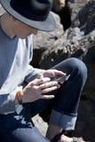 Le jeune homme dans le chapeau noir vérifie des messages sur le smartphone Photographie stock libre de droits