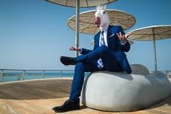 Le jeune homme dans le costume s'assied sous des parapluies sur le bord de mer de ville images stock
