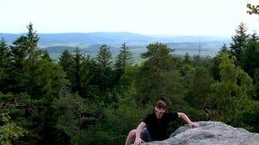 Le jeune homme dans des lunettes de soleil s'élèvent sur la roche en pierre dans le paysage tchèque clips vidéos