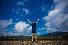Le jeune homme dans des lunettes de soleil se tient contre le ciel bleu Photo stock