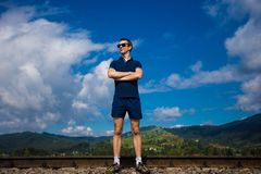 Le jeune homme dans des lunettes de soleil se tient contre le ciel bleu Photos stock