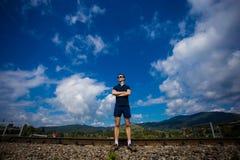 Le jeune homme dans des lunettes de soleil se tient contre le ciel bleu Image stock