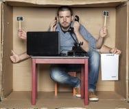 Le jeune homme dans la boîte de bureau est très un multitâche Photo libre de droits