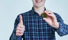 Le jeune homme dans la chemise bleue tient le bitcoin et montre le pouce augmenté D'isolement sur le fond blanc Le concept du bit image libre de droits