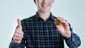 Le jeune homme dans la chemise bleue tient le bitcoin et montre le pouce augmenté D'isolement sur le fond blanc Le concept du bit photographie stock