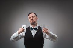 Le jeune homme dans la chemise et le gilet montre ses cartes de tisonnier, tir de studio Photographie stock