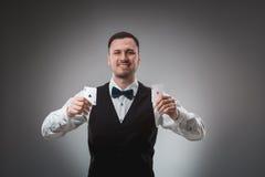 Le jeune homme dans la chemise et le gilet montre ses cartes de tisonnier, tir de studio Photo stock