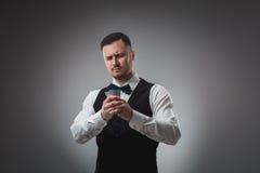 Le jeune homme dans la chemise et le gilet observent ses cartes de tisonnier, tir de studio Photographie stock libre de droits
