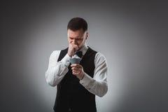 Le jeune homme dans la chemise et le gilet observent ses cartes de tisonnier, tir de studio Images stock