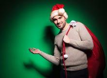 Le jeune homme dans le chapeau de Santa se présente Photo stock