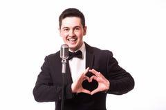 Le jeune homme dans le costume chantant avec le microphone et font le signe d'amour avec des mains Images stock