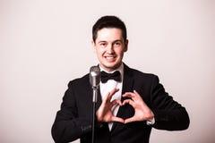 Le jeune homme dans le costume chantant avec le microphone et font le signe d'amour avec des mains Images libres de droits