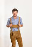 Le jeune homme dans le pantalon en cuir est heureux Image stock